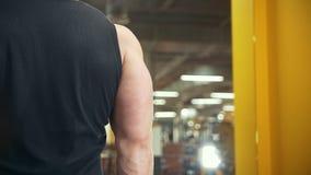 Den bakre sikten av den muskulösa mannen lyfter en hantel i en idrottshall arkivfilmer