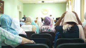 Den bakre sikten av muslimkvinnor i hijab på det islamiskt masssamlar stock video