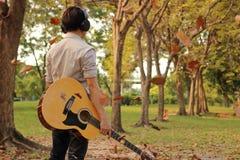 Den bakre sikten av ståenden av den stiliga unga mannen som rymmer den akustiska gitarren med hörlurar mot bland fallande sidor i Royaltyfri Bild