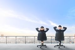 Den bakre sikten av två asiatiska affärspersoner som sitter på kontorsstolen i modern terrass, kopplar av och ser sikt på staden arkivbilder