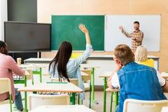 den bakre sikten av unga studenter som lyssnar till lärare, föreläser royaltyfri fotografi