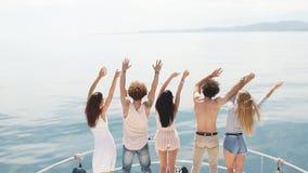 Den bakre sikten av vänner firar på segelbåten i havet, lyftta armar lager videofilmer
