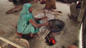 Den bangladeshiska kvinnan producerar torra stekte ris på varm sand i en traditionell stätta i Tangail, Bangladesh lager videofilmer
