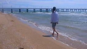 Den barfota kvinnan går till pir på den sandiga stranden i blåsig solig dag på havet stock video