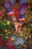 Den barfota kvinnan lägger benen på ryggen i yoga poserar i färgrik ou för höstsidor arkivfoto