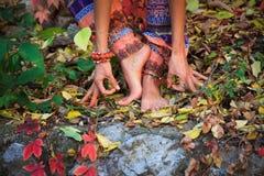 Den barfota kvinnan lägger benen på ryggen, och händer i yoga och mudra gör en gest i colo royaltyfri fotografi