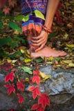 Den barfota kvinnan lägger benen på ryggen, och händer i yogaelasticitet poserar i färgrikt royaltyfria foton