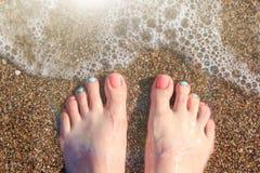 Den barfota kvinnliga foten med en ljus pedikyrnärbild på en grund havssingel på vatten`en s kantar Fotografering för Bildbyråer