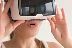 Den barn förbluffade kvinnan som bär VR-hörlurar med mikrofon, välter tror henne ögon Royaltyfria Foton