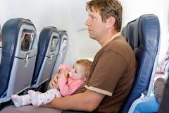 Den barn tröttade fadern bär hans behandla som ett barn dottern under flyg på flygplanet Fotografering för Bildbyråer