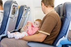 Den barn tröttade fadern bär hans behandla som ett barn dottern under flyg på flygplanet Arkivbild