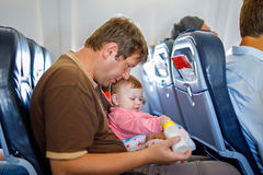 Den barn tröttade fadern bär hans behandla som ett barn dottern under flyg på flygplanet Arkivfoton