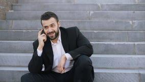 Den barn uppsökte affärsmannen som talar på mobiltelefondanande, handlar sammanträde på trappa i gata royaltyfri foto