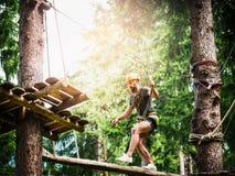 Den barn uppsökte grabben klättrar på repet i klättringskog på härlig naturbakgrund Royaltyfria Bilder