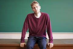 Den barn uppsökte studenten sitter på läraretabellskrivbordet framme av svart tavla med kopieringsutrymme Fotografering för Bildbyråer