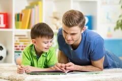 Den barnpojken och farsan läste en bok på golv hemma Arkivbild