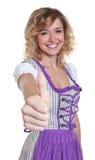 Den bayerska kvinnan med lockig visning för blont hår tummar upp Royaltyfri Foto