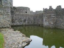 Den Beaumaris slotten fördärvar och vallgraven Arkivfoto