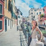 Den Beautful flickan är Stadning vid floden i Venedig, Italien Royaltyfri Foto