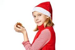 Den Beautyful flickan i röd jultomtenhatt med guld- sörjer kottar Arkivfoto