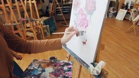 Den begåvade konststudenten blandar färger på paletten som målar därefter blommor på kanfas, medan hennes yrkesmässiga lärare är arkivfilmer