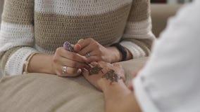 Den begåvade kvinnan målar kvinnliga händer vid hennamehndigarneringar lager videofilmer