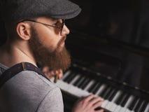 Den begåvade skäggiga musikern spelar pianot arkivfoto