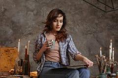 Den begåvade unga konstnären läraren i ett avbrott betraktar det ofullständiga arbets- och drinkteet Hon drar olja och akryl Royaltyfri Fotografi