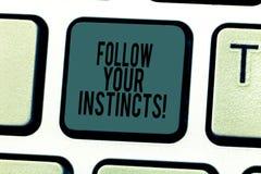 Den begreppsmässiga handhandstilvisningen följer dina instinkter Affärsfototext lyssnar till din intuition och lyssnar till ditt arkivfoto