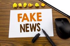 Den begreppsmässiga visningen för handhandstiltext fejkar nyheterna Affärsidé för Hoax journalistik som är skriftlig på klibbigt  royaltyfri bild