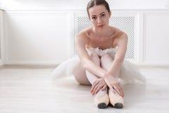 Den behagfulla ballerina sitter på golvet, balettbakgrund Royaltyfri Bild