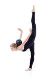 Den behagfulla gymnasten med klumpa ihop sig på tillbaka stativ på ett lägger benen på ryggen Royaltyfri Fotografi