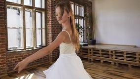 Den behagfulla unga ballerina i vita klänningballerinakjol- och pointeskor utförde balettdans Den unga ballerina är att göra som  lager videofilmer