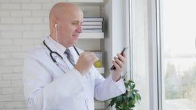 Den behog doktorn avbildar göra en påringning genom att använda smartphonen och hand-fritt stock video