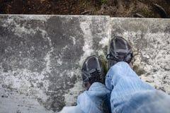 den Beinen und Füßen unten betrachten, die auf einer Leiste stehen Lizenzfreies Stockbild
