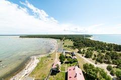 Den bekväma stranden av det baltiska havet med vaggar och grön vegetat Royaltyfria Bilder