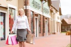 Den bekymmerslösa damen som går med, shoppar packar royaltyfria bilder