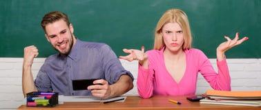 Den bekymmerslösa grabben och flickan sitter på skrivbordet i klassrum Studera i högskola eller universitet Vänstudenter som stud royaltyfria bilder