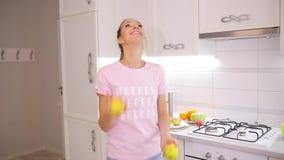 Den bekymmerslösa helgen kvinna jonglerar äpplen på ett kök hemma lager videofilmer