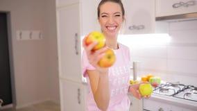 Den bekymmerslösa helgmorgonen kvinna jonglerar äpplen på ett kök hemma stock video
