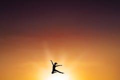 Den bekymmerslösa kvinnan hoppar på skymningtid fotografering för bildbyråer