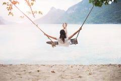 Den bekymmerslösa lyckliga kvinnan på gunga på härliga paradis sätter på land Royaltyfri Fotografi