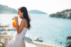 Den bekymmerslösa unga kvinnlign på feriesommarsemestern som har gyckel på en solig dag och att koppla av med havsikten som lyssn Royaltyfri Foto