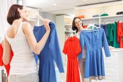 Den bekymmerslösa flickan som väljer kläder shoppar in Arkivbilder