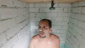 Den bekymrade caucasianen skummade den unga mannen, efter vattnet i duschen vändes av Stängda av duschsammanbrott eller varmvatte lager videofilmer