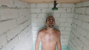 Den bekymrade caucasianen skummade den unga mannen, efter vattnet i duschen vändes av Stängda av duschsammanbrott eller varmvatte stock video