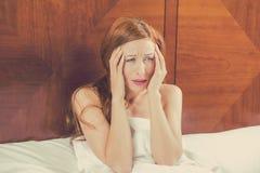 Den bekymrade unga kvinnan som lägger i säng, kan inte falla sovande har huvudvärk royaltyfri fotografi