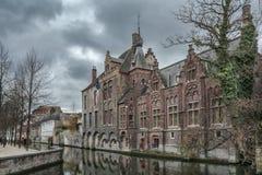 den Belgien brugge byggnadsdörren blommar gammala röda townfönster Royaltyfri Fotografi