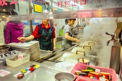 Den berömda kinesiska nudeln shoppar och den Unacquainted kinesiska kocken som lagar mat i 'den beijing vägen 'som går gatan i de royaltyfri bild