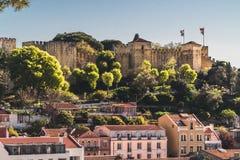 Den berömda medeltida slotten av St George överst av en kulle i staden av Lissabon, Portugal Är under några modernare byggnader i royaltyfri bild